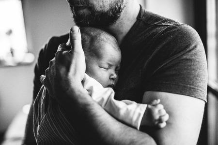 Padre irriconoscibile a casa che tiene la sua neonata. Archivio Fotografico - 79897312