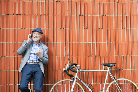 Senior man with smartphone and bicycle against brick wall. Stock Photo