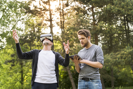 computer simulation: Young man and his senior father with VR glasses outdoors. Stock Photo