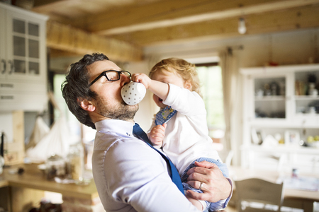 Businessman holding little son in the arms, drinking coffee. Stock fotó - 80107560