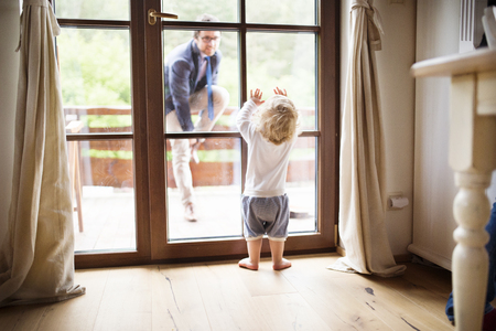 Businessman coming home, little son at the door welcoming him.