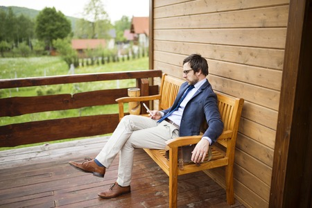 Businessman with smart phone sitting on front porch. Stock Photo