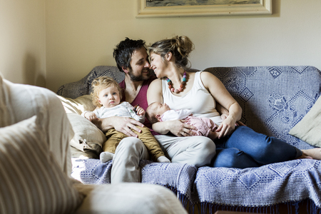Young parents on couch with their cute little children Stock Photo