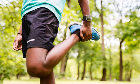 afroamerican: Unrecognizable afro-american man in park stretching legs. Stock Photo