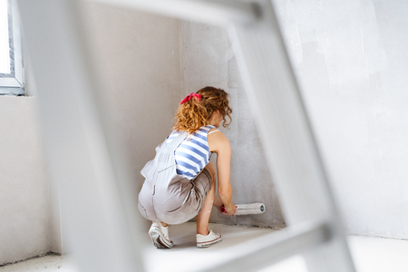 Young woman painting walls of her new house.