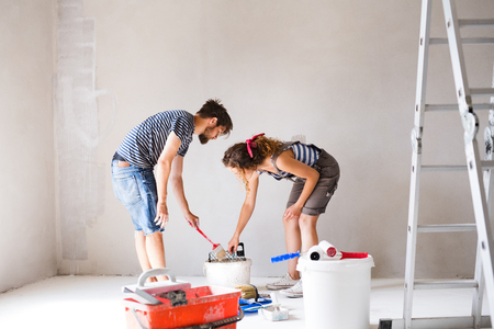 Young couple painting walls in their new house. Banque d'images