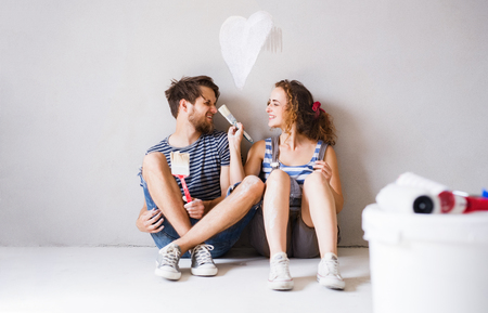 roller: Young couple in love painting walls in their new home. Stock Photo