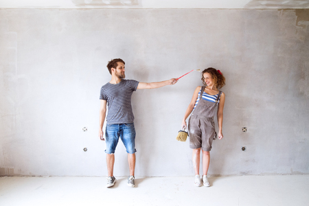Young couple in love painting walls in their new home. Stok Fotoğraf