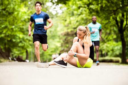 足関節捻挫との競争に若い女性は。