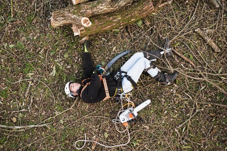Injured lumberjack with chainsaw lying on the ground after fall Imagens