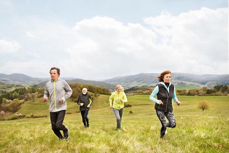 Groep senioren die buiten op groene heuvels lopen.