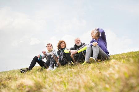 Groep senior runners in openlucht, rusten en praten. Stockfoto