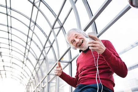 スマート フォンと通路でヘッドフォンと年配の男性。