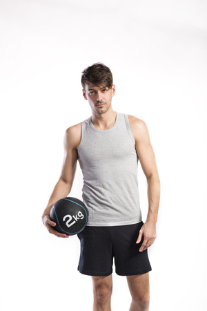Handsome fitness man holding medicine ball, studio shot. Banco de Imagens