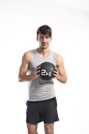 Handsome fitness man holding medicine ball, studio shot. Banco de Imagens