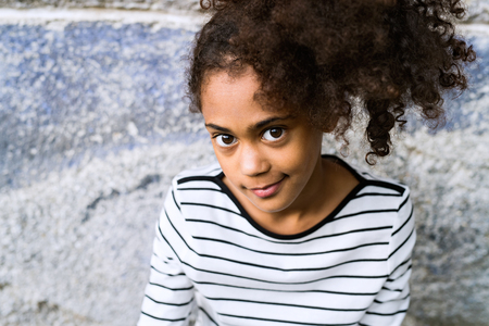 long sleeved: African american girl in striped t-shirt against concrete wall.