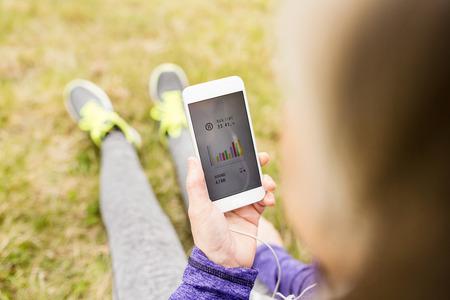 Onherkenbare actieve senior runner in de natuur met slimme telefoon.