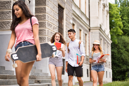Group of attractive teenage students walking to university.