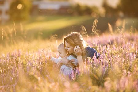 自然に腕の中での赤ちゃんの息子の若い母親。 写真素材