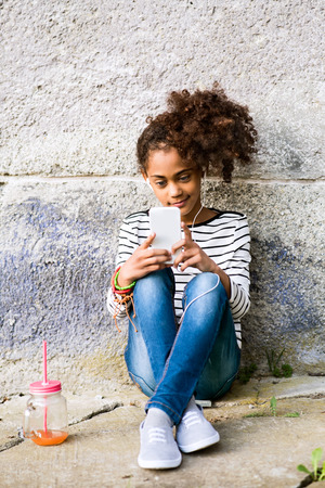 Beautiful african american girl with smart phone and drink. Фото со стока