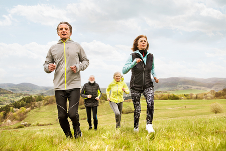 Group of seniors running outside on green hills. Stock Photo