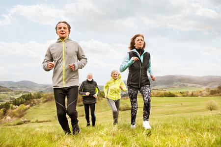 Group of seniors running outside on green hills. Standard-Bild