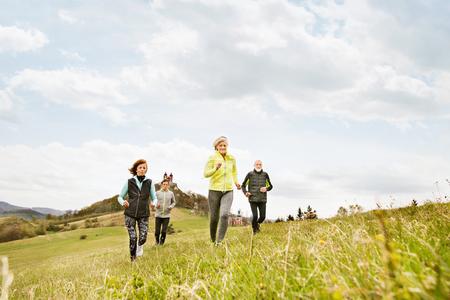 Group of seniors running outside on green hills. Stock Photo