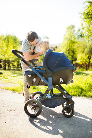 Father with little son and baby daughter in stroller. Sunny park Stock Photo
