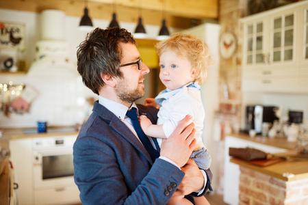 Zakenman komt thuis, houdt zoontje in de armen. Stockfoto