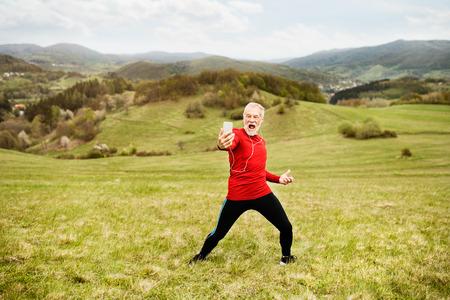 Actieve senior runner in de natuur die zelfde met slimme telefoon neemt. Stockfoto