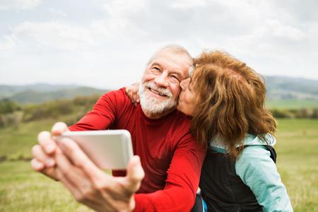 sweatshirt: Active senior runners in nature taking photo with smart phone.