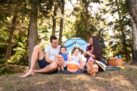 Beautiful young family with daughters camping in forest. 版權商用圖片