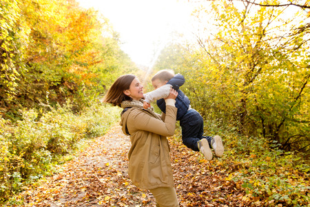 Beautiful young mother with her son in autumn forest. Stok Fotoğraf