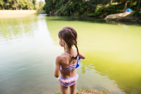 Little girl standing at the lake. Sunny summer.
