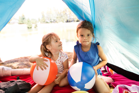 Beautiful little girls in tent camping by the lake. Banco de Imagens