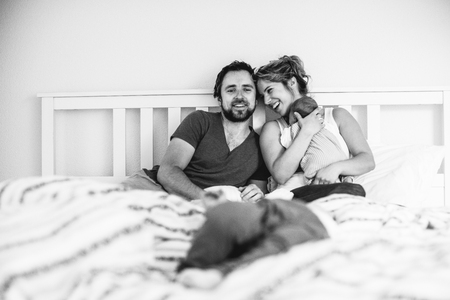 Young parents in bed with their cute little children photo