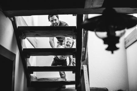 Vater zu Hause mit seinem kleinen Sohn, der langsam die Treppe hinaufgeht. Standard-Bild - 82724643