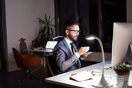 Businessman in the office at night drinking coffee. photo