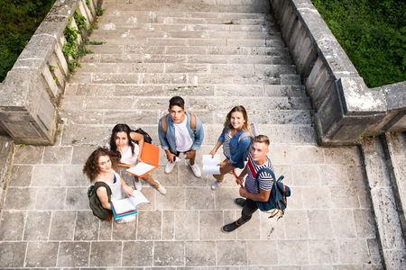 Teenage students at the stone steps in front of university.