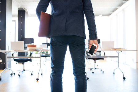 Businessman in his office with smartphone and briefcase. photo