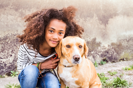 African american girl with her dog against concrete wall.