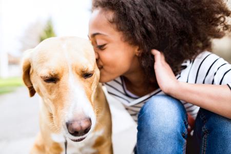 Afrikaans Amerikaans meisje dat in openlucht met haar hond, hem kust.