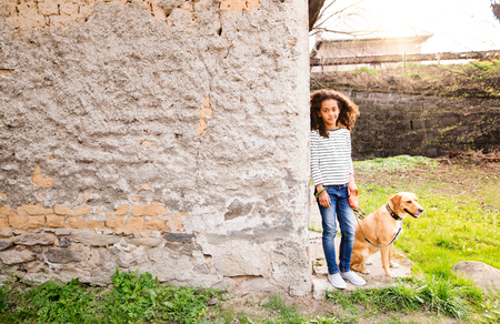 African american girl with her dog at the concrete wall. Фото со стока