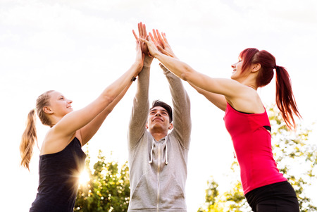 Group of young runners in park doing high five gesture. Stock Photo