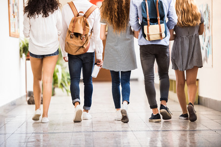 Unrecognizable teenage students in high school hall. Stock Photo - 84105541