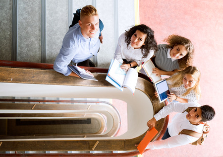 Teenage students on stairs in high school. Stock Photo