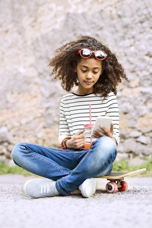 Beautiful african american girl with smartphone and skateboard. Stock Photo