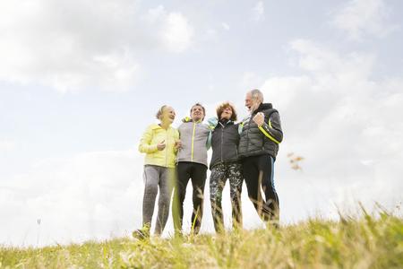 上級ランナー屋外の休憩、腕周りを保持しているグループ。