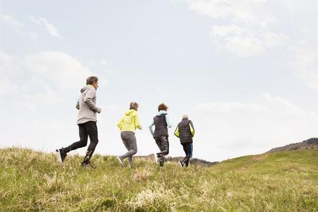 Group of seniors running outside on the green hills. 版權商用圖片