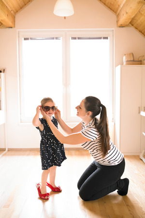 Mother puts on sunglasses to her cute little daughter.